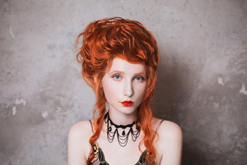 A woman with red hair in a nightgown. Red-haired girl with pale skin and blue eyes with bright unusual appearance with choker around her neck on a background of gray wall. French courtesan. Copyspace