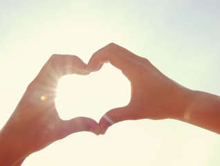 Female hands in the form of heart against the sky. Hands in shape of love heart