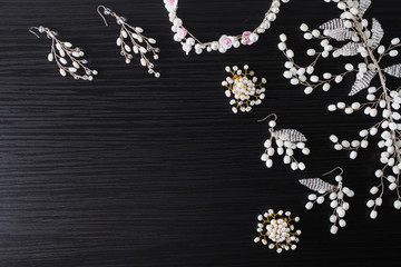Jewelery for hair and white earrings made of beads on a dark background. Women's jewelry.