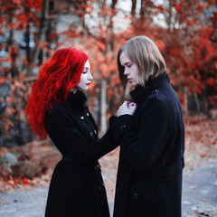Informal guy with long hair and a woman with long red curly hair in a black coat. Red-haired girl with pale skin, blue eyes with bright unusual appearance and a sweet face. Goths