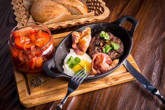 Frying pan, fried eggs, bread, steak, bacon and tomatoes
