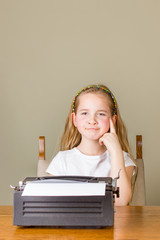 Young blonde girl thinking about something while working on a black vintage typewriter at home