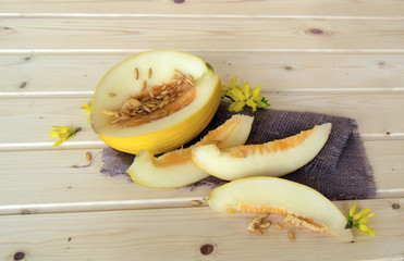 The fresh, juicy, ripened melon lies on a wooden table.