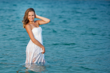 Beautiful woman standing in the sea in white dress. Pretty girl got wet her dress in the sea water. Attractive woman smiling at camera.