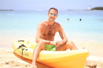 Homme sur un canoé jaune devant la mer turquoise