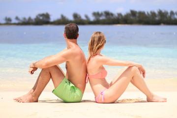 Couple en maillot devant une mer turquoise