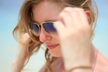 Jeune femme tenant ses lunettes de soleil