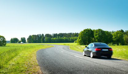Wall Mural - Car on asphalt road in beautiful spring day at countryside