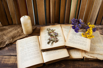 Old books, candle and flowers on wooden table