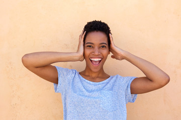 young african woman laughing with hands behind head