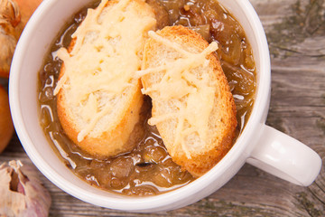 Onion soup with toast on a wooden background with some onions and garlic