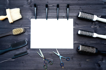 Hairdresser tools on wooden background. Blank card with barber tools flat lay. Top view on wooden table with scissors, comb, hairbrushes and hairclips with empty white paper, free space. Barbershop