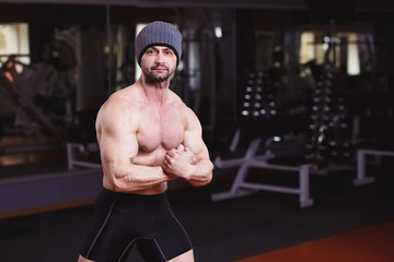 Strong healthy adult ripped man with big muscles posing in gym