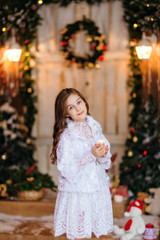 cute young long-haired girl in a white dress standing, holding in his hand a candle on the background of Christmas decorations