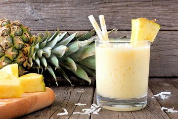 Healthy pineapple smoothie in glass, scene against an old wood background