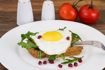 Breakfast toast with fried egg and arugula
