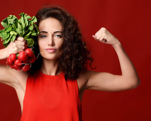 Pretty cheerful young sport woman posing with fresh radish green leaves