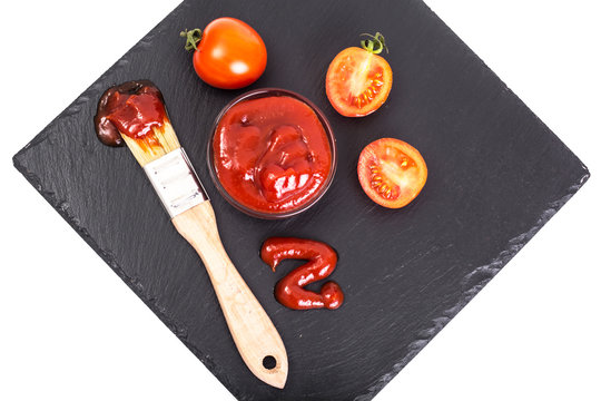 Bowl with  ketchup, tomatos  and brush on black stone background