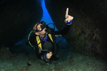 Blonde woman scuba diver explore coral reef in ocean