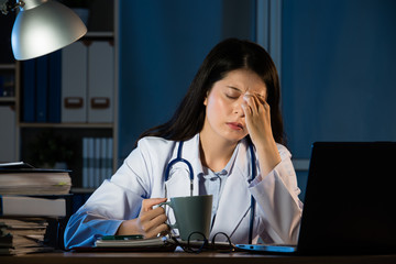 unhappy doctor with headache stressed holding coffee