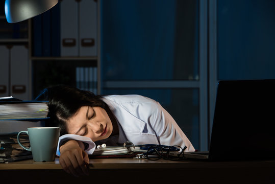 doctor feel tired sleeping on desk of clinic