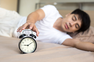Man reaching out for alarm clock on morning.