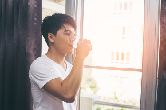 Asian man drinking water at the morning, vintage color tone.
