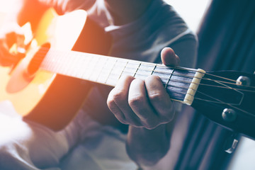 Man's hands playing guitar, close up, vintage color tone.
