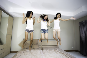 Cheerful young asian woman jumping on the bed at home