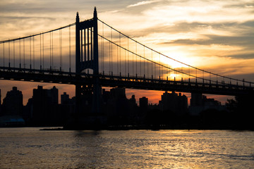 Triborough bridge and city with sunset in silhouette, New York