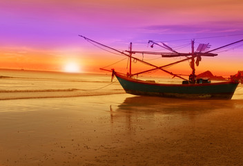 A beautiful sunset seen the fishing boat lies at beach.