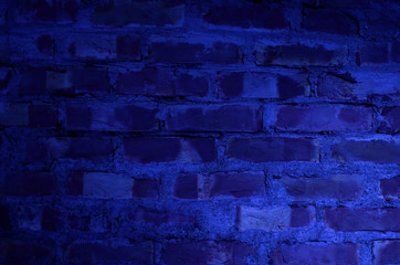 Mysterious blue brick wall with light in dark night.