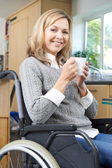 Disabled Woman Sitting In Wheelchair At Home With Hot Drink