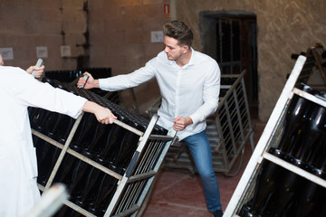 Worker transporting  bottles of wine at sparkling wine industry