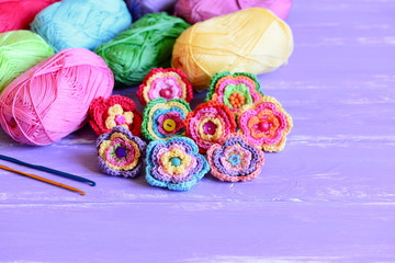 Colorful crochet flowers set. Bright crochet flowers, varicolored cotton yarn, crochet hooks on wooden background with copy space for text. Easy handmade decorations concept. Closeup
