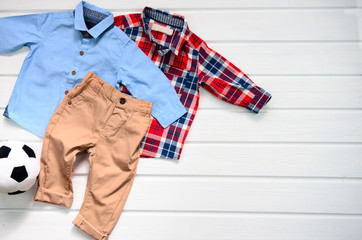 Baby boy clothing set (blue shirt, plaid red shirt and brown pant). Wish list or shopping overview for pregnancy and baby shower. View from above