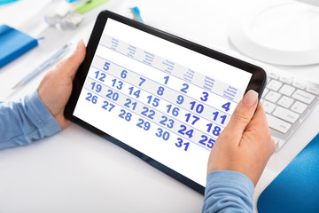 Woman Looking At Calendar On Digital Tablet