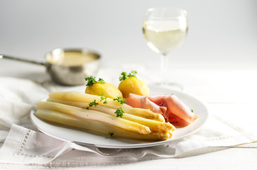 Juicy white asparagus dish with potatoes and ham on a white plate, sauce hollandaise and wine blurred in the bright background, copy space
