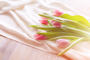 Pink tulips on white fabric, lit by the rays of the setting sun