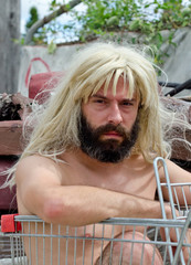 Homeless man wearing blonde wig and sitting in trolley