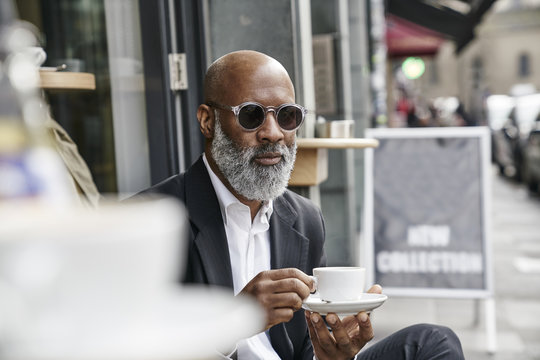 Mature businessman drinking coffee in pavement cafe