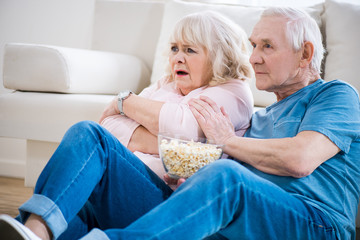 senior couple sitting on floor with popcorn and watching tv, frightened woman.