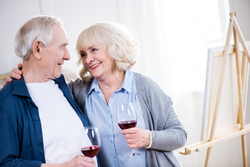 portrait of smiling senior couple drinking wine in art workshop
