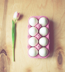 Easter eggs and tulip flower - toned image, flat lay, top view.