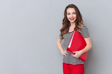 Happy young lady standing over grey wall and holding folder