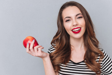 Happy young lady walking over grey wall and holding apple.