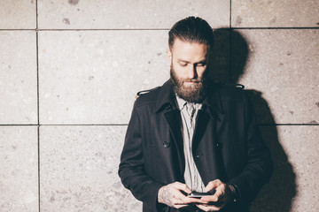 Young handsome caucasian bearded businessman using smart phone