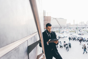 Young handsome caucasian bearded businessman using tablet