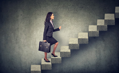 Businesswoman with briefcase stepping up a stairway career ladder