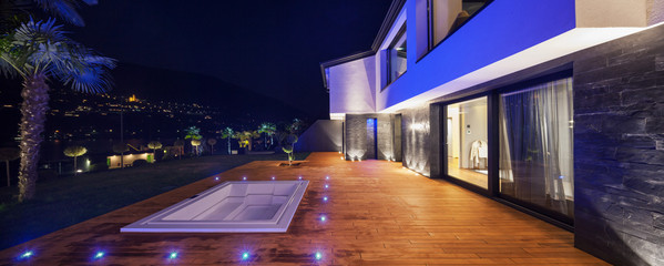 View of modern villa in the night with pool